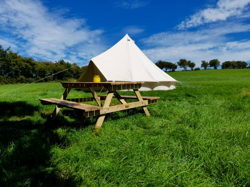 A bell tent, pitched on one of the seven grass camping pitches at Coedfryn Farm.